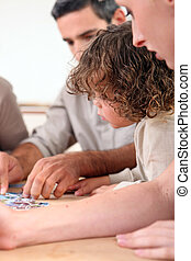 Family completing jigsaw at home