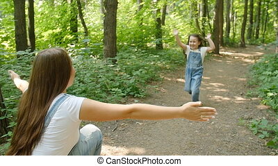 Family concept. Cute baby girl runs to Mom's embrace in the park