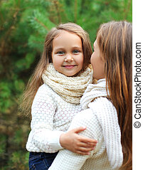 Family concept - happy mother and child having fun together in winter day