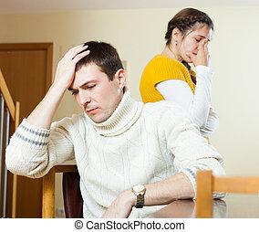 Sad young ordinary man and  crying  woman at home