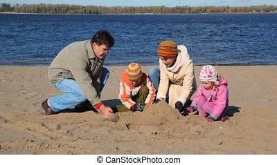 family constructing sand buildings on beach