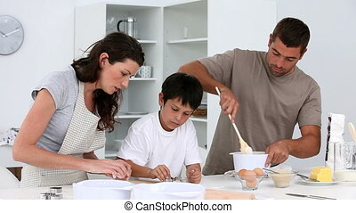 Family cooking biscuits together in the kitchen