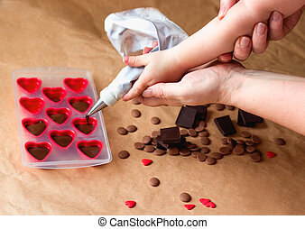 Family cooking class. Mommy and me Handmade valentines day dessert. Making chocolate candy,Kids Hands filling hearts