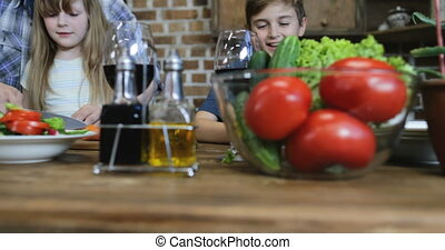 Family Cooking Together In Kitchen Parents With Two Kids Preparing Food At Home Talking Chopping Vegetables For Salad
