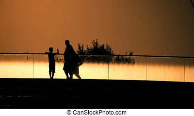 Family Couple and Child Crossing Bridge Sunset Back Lit...