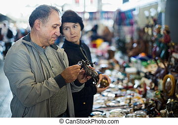 Family couple buying retro artifacts at the antique market