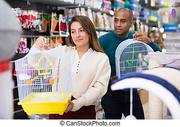 Family couple choosing bird cage at store