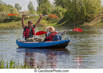 Family couple is kayaking on the river