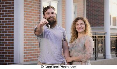 Family couple near the house. He shows keys, she embraces...