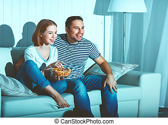 Family couple watching television at home on sofa