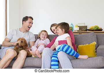 Family Cuddles at Home - Family of four are sitting on the...