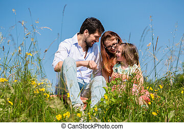 Family cuddling sitting on meadow