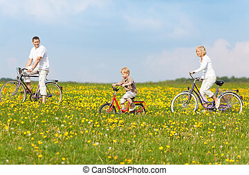 family cycling through nature - happy family cycling through...
