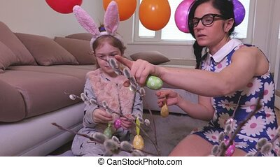 Family decorate pussy willow with Easter eggs