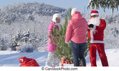 Family decorates a Christmas tree in snow covered winter forest
