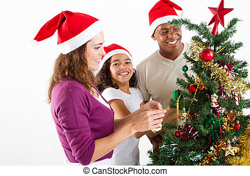 family decorating Christmas tree - happy multiracial family...
