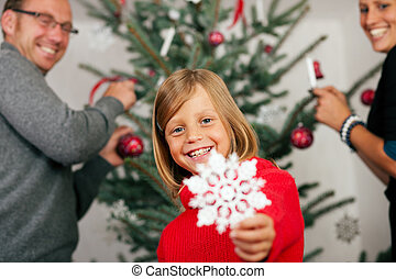 Family decorating the Christmas Tree