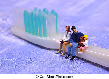 Miniature People Sitting on a Toothbrush. Family Dentistry Concept.