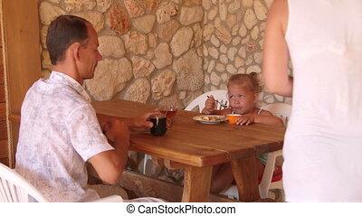 Family dinner in outdoor summer kitchen
