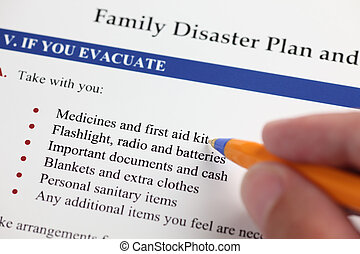 Family Disaster Plan and hand with ballpoint pen. Close-up.