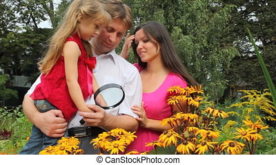 Family discover some plants with magnifying glass