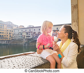 Happy mother and daughter eating ice cream near Ponte Vecchio