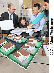 Family discussing a housing development with an architect