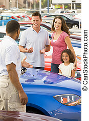 Family discussing new car with salesman on lot