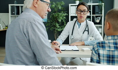 Family doctor in uniform is talking to little boy and grandfather in hospital office giving medical advice. Communication, people and medicine concept.