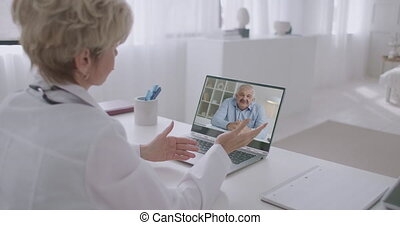 family doctor is talking with male patient by laptop, using video call, man is speaking about his health and illness