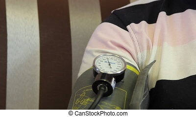 Family doctor measures patient's blood pressure.