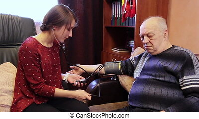 Family doctor at the hospital measures patient's blood pressure. An old sick man has a bad heart.