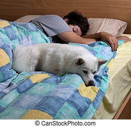 Family dog sleeping with teen girl on bed