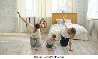 Family doing gymnastic exercises in bedroom at home - healthy life education of their little son