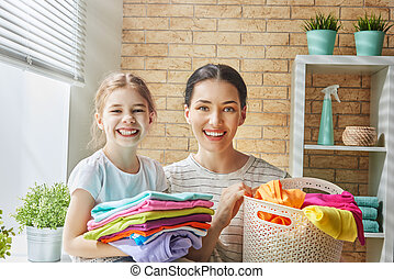 family doing laundry at home - Beautiful young woman and...
