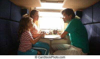 Family drinks tea in train.