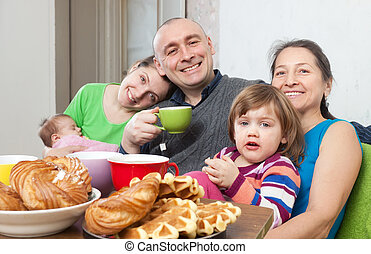 family drinks tea with baked at home