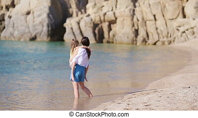 Family during on beach on greek vacation. Mother and kid enjoy summer by the sea