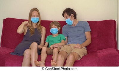 Family during quarantine watch tv sitting on a couch. Self-isolation concept.