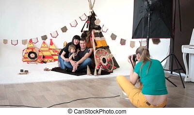 back view of photographer taking shots of family at wigwam. Studio shot.