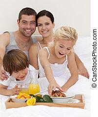 Family eating nutritive breakfast in bedroom