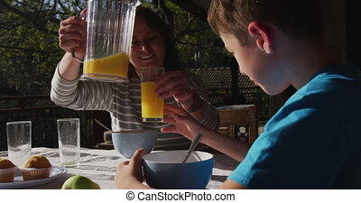 Family eating breakfast together outdoors - Front view of a ...