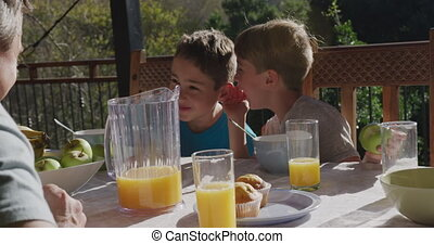 Family eating breakfast together outdoors - Front view of ...