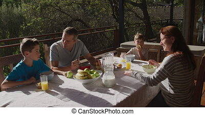 Family eating breakfast together outdoors - High angle view ...