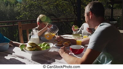 Family eating breakfast together outdoors - Side view of a ...