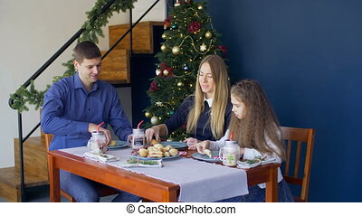 Family eating christmas cookies at festive table