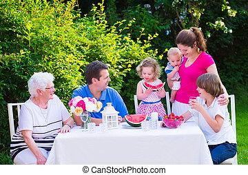 Family eating fruit in the garden