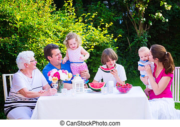 Family eating fruit in the garden - Happy big family - young...