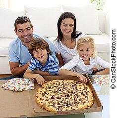 Family eating pizza on sofa