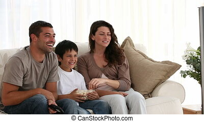 Family eating pop corn on the sofa
